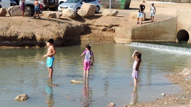 ילדים רוחצים בבריכה מזוהמת