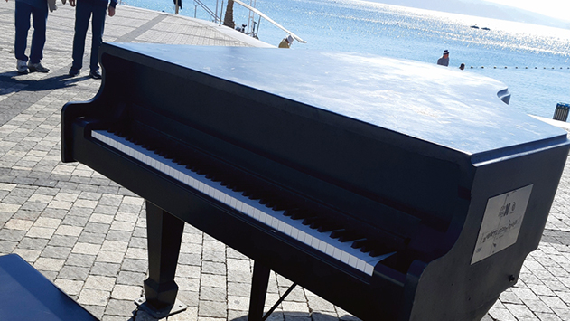 מכסה פסנתר הרחוב על טיילת התיירות קטע חלק מאצבעה של המנגנת